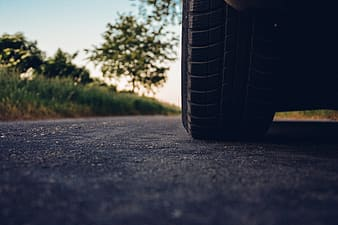 Low-angle photography of vehicle tire on the middle of the road
