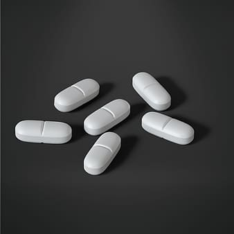 Six oval white medication tablets
