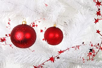 Two red baubles on white Christmas tree