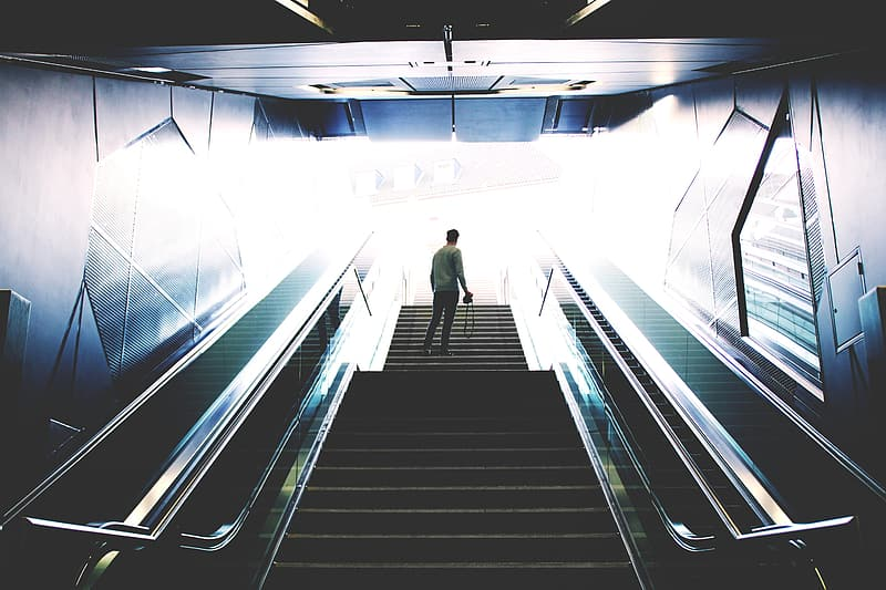 Man in white shirt and black pants standing on escalator