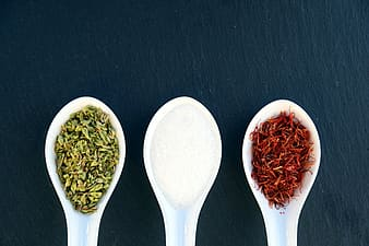 Three white plastic spoons with spices