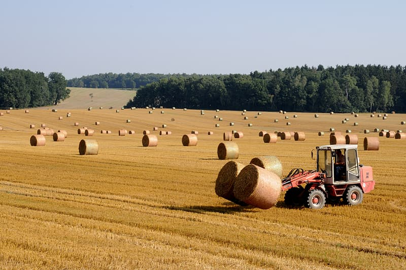 Red tractor with hay stacks on brown field during daytime