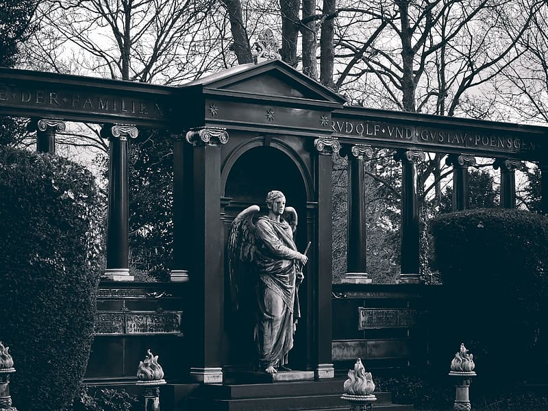 Grayscale photo of angel standing and holding sword statue