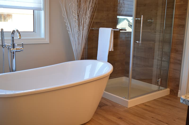 White ceramic bathtub beside a clear glass shower enclosure and an open window