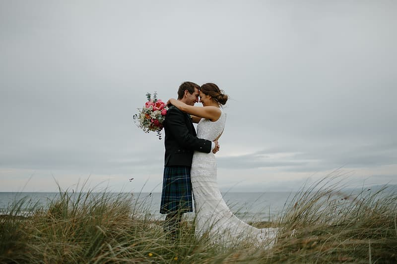Groom and bride on top of grassy hill hugging