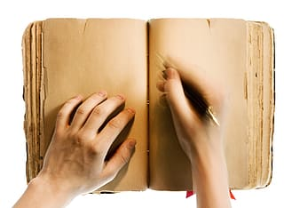 Person writing on white book