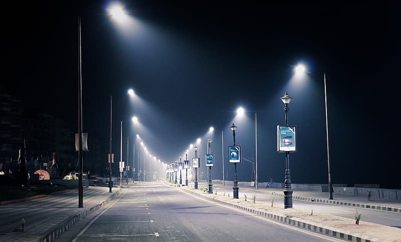 Roadside parking lot with streetlamps during nighttime