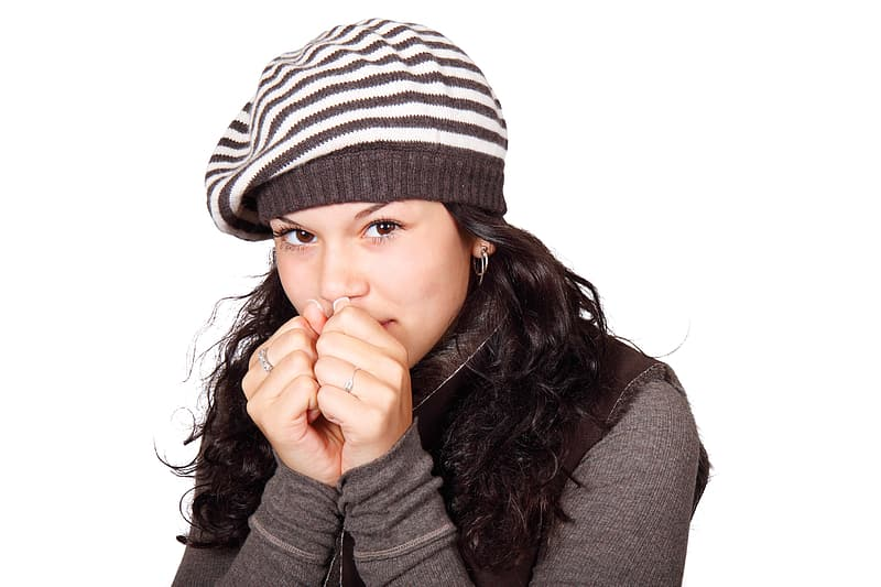 Woman with white and black striped knit cap and black long-sleeved top