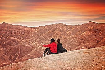 Two women sitting on hill looking at hills