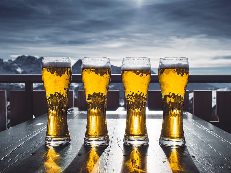 Four beer mugs on table and mountain at distance