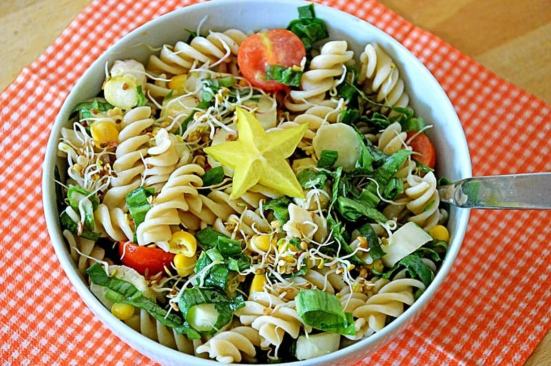 Pasta with vegetables in round white ceramic bowl