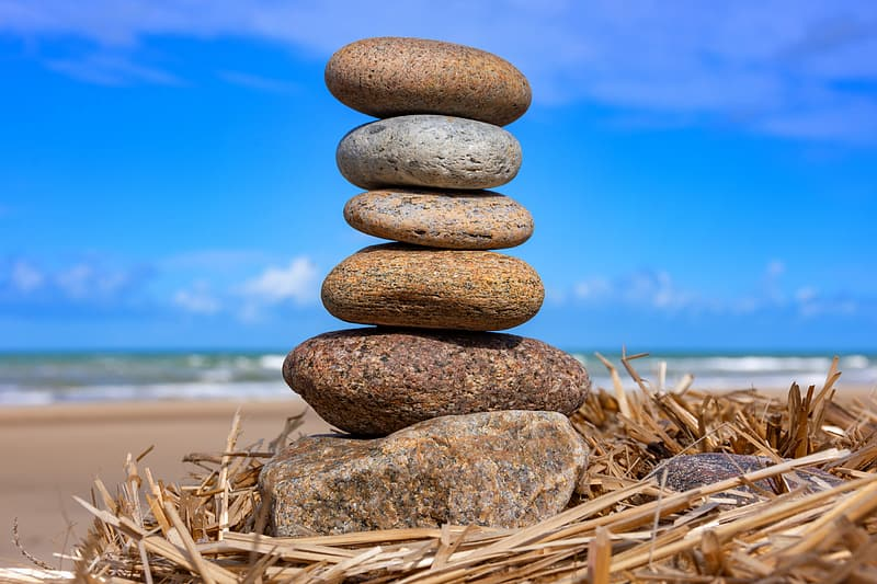 Stack of stones on seashore during daytime