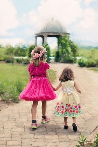 Two girls walking through gray gazebo during daytime