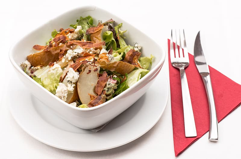 Vegetable salad in white bowl on white plate with fork and knife