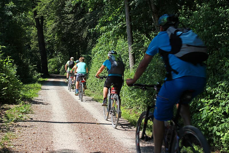 People riding bicycle on dirt road during daytime