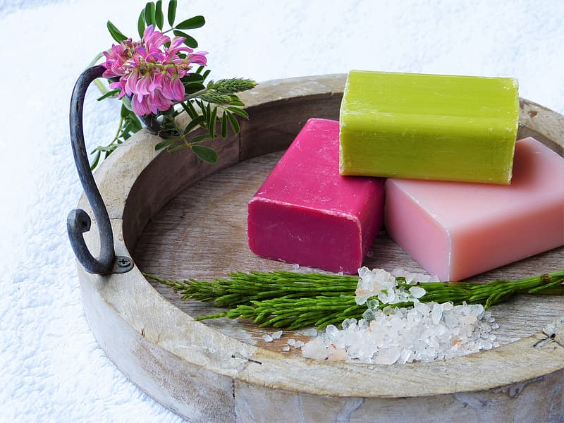 Green, red, and pink soap on brown tray