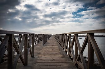 Brown wooden dock under cloudy sky during daytime