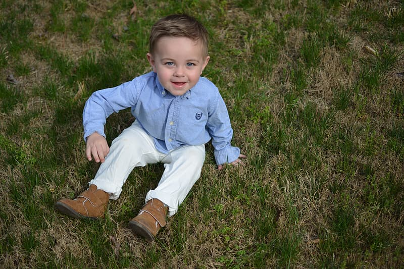 Boy in blue zip up hoodie and white pants sitting on green grass field during daytime