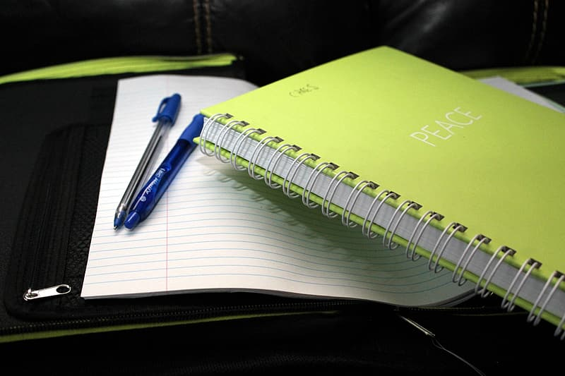 Blue click pen on white spiral notebook
