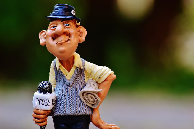 Shallow focus photography of brown-haired man holding white microphone bobblehead display figure