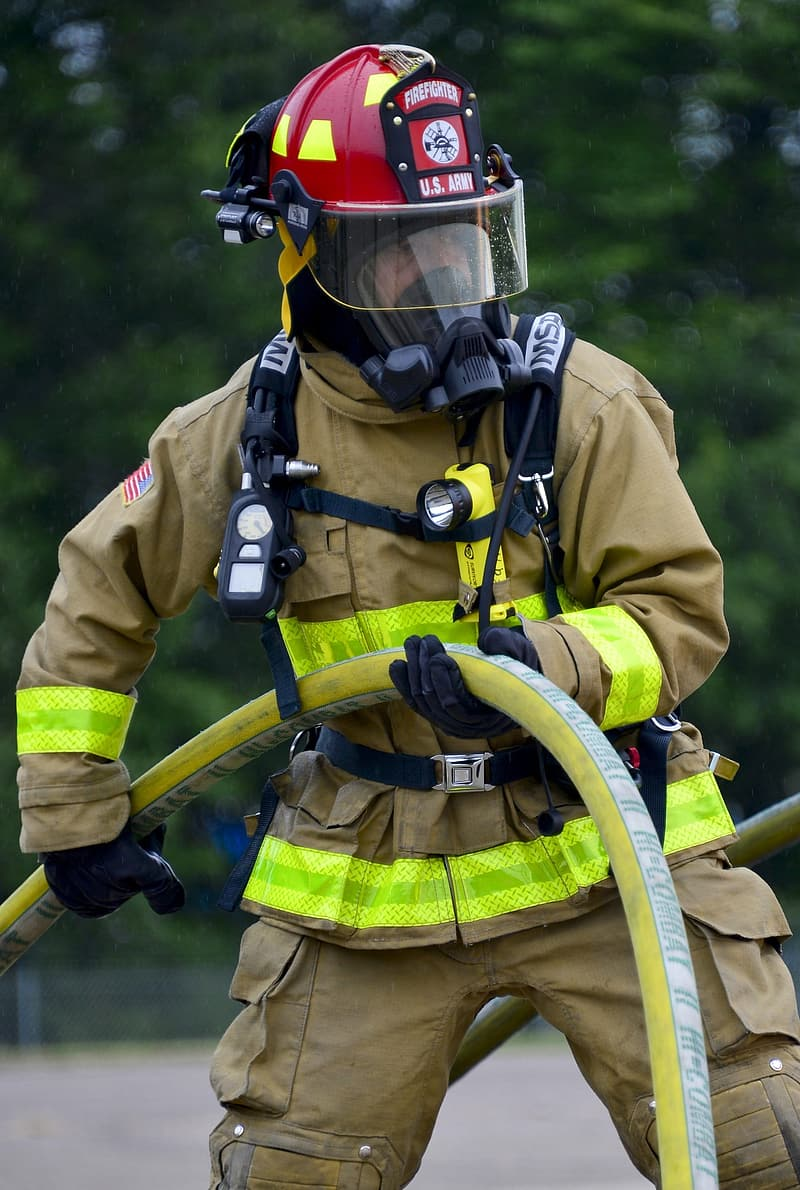 Man wearing bunker suit holding hose