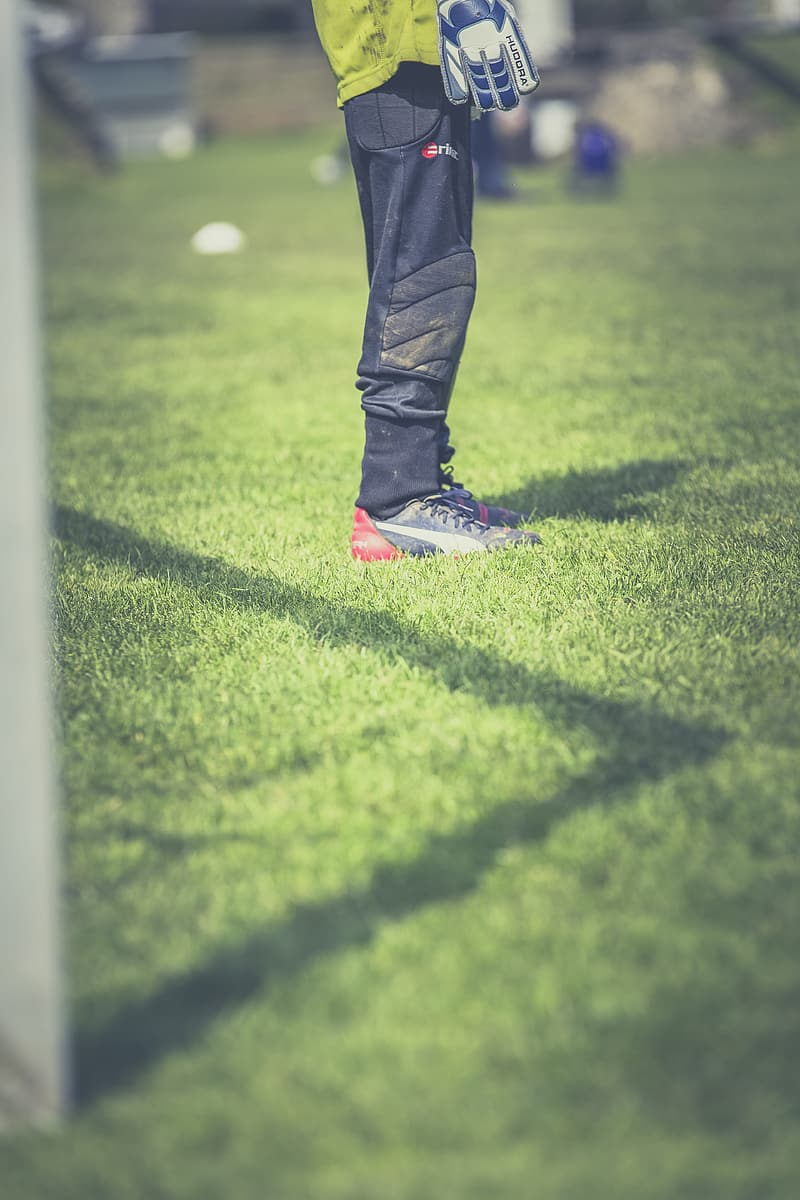 Person in black pants and black and white nike shoes standing on green grass field during