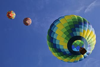 Low angle view of three hot air balloons in mid air under blue sky