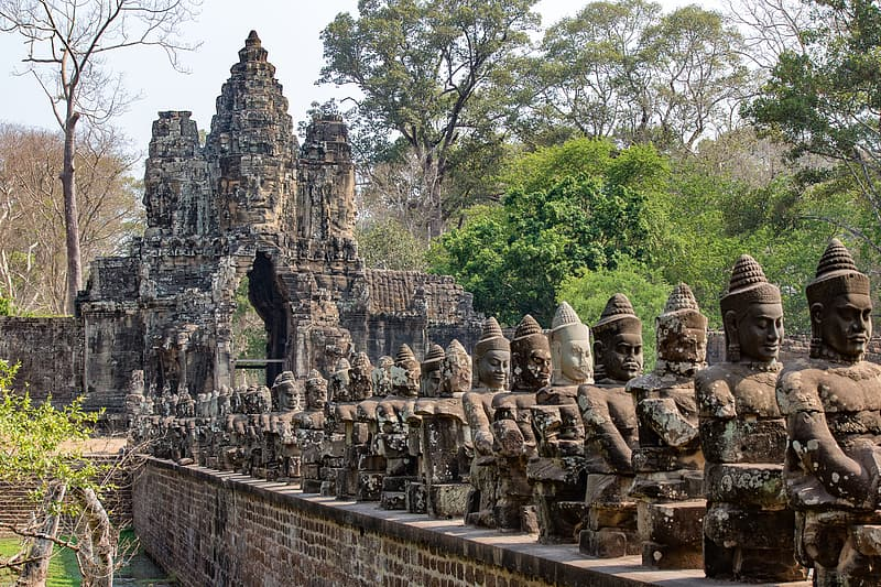 Piled statues beside trees