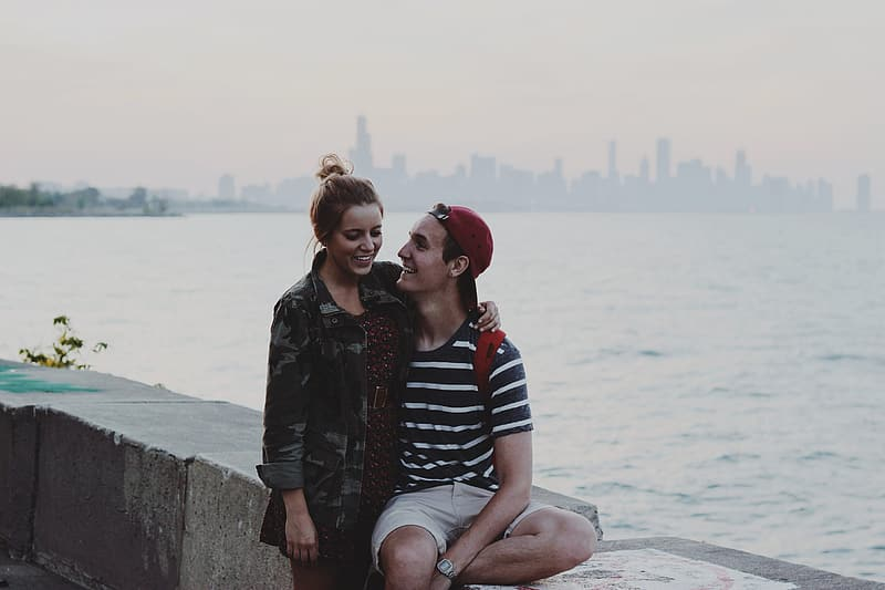 Man and woman sitting on concrete wall near body of water during daytime