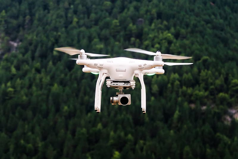 White drone flying over green trees during daytime