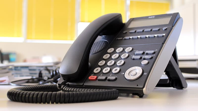 Black caller ID telephone on white surface