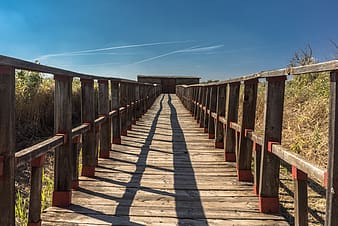Brown wooden bridge under clear blue sky during daytime