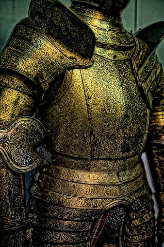 Gold knight armor near gray painted wall