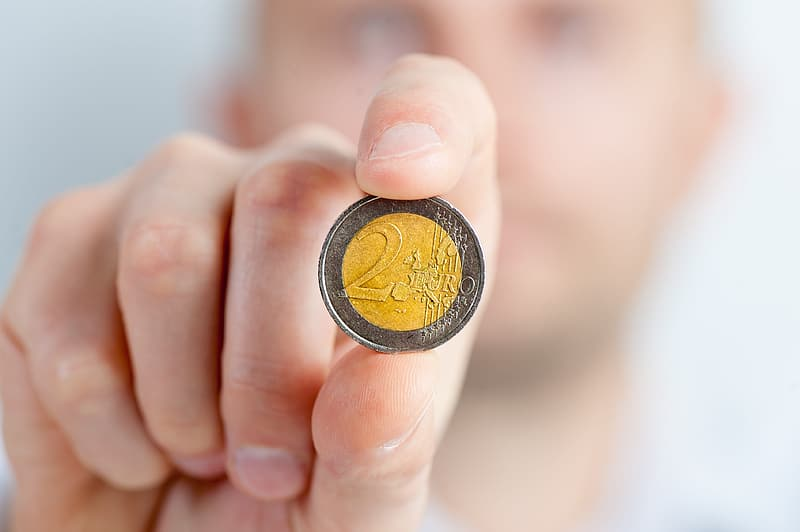 Person holding round silver and gold-colored 2 coin