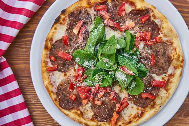 Pizza with green leaves on brown ceramic plate