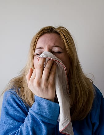 Woman covering nose a white handkerchief