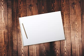 Brown wooden pencil with white notebook