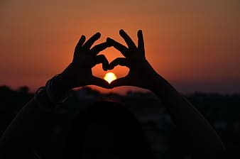 Silhouette of person hand form heart