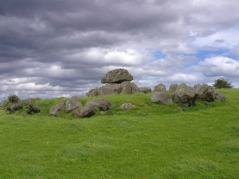 Gray rocks on green grass field under white clouds during daytime