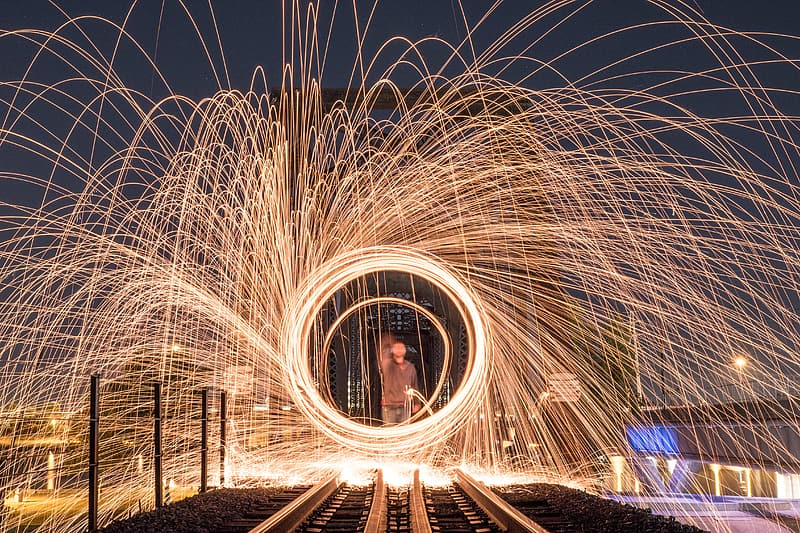 Man in front of train railroad steel wool photography