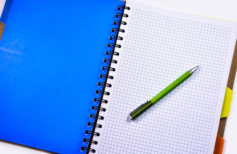 White graphing notebook and green click pen