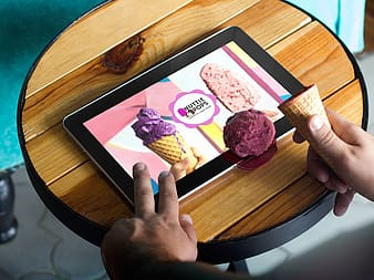 Person holding tablet computer showing Nuttie Pops advertisement