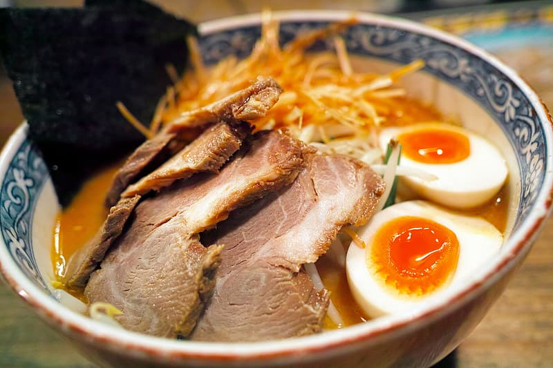 Meat with egg and noodles on bowl