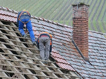 Two person putting roof tiles on roof at daytime