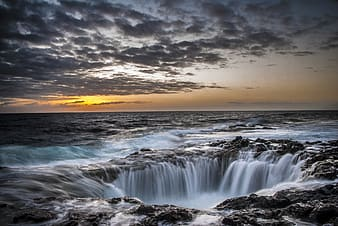 Water falls under gray clouds during sunset