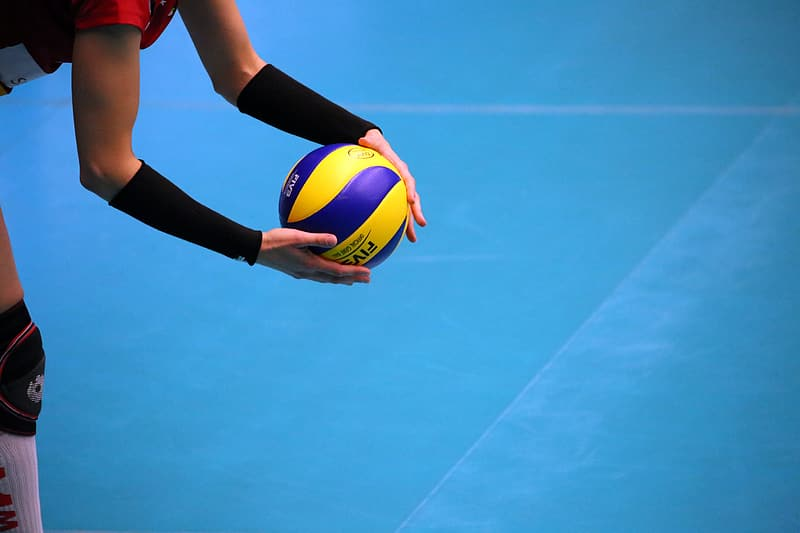 Woman in black leggings and red shirt holding yellow and blue volleyball