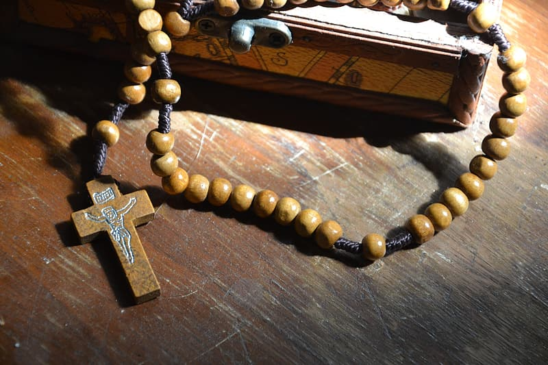 Brown rosary on brown wooden board