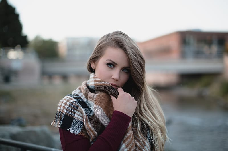 Woman wearing marono long-sleeved top and white and brown plaid scarf taking photo during daytime