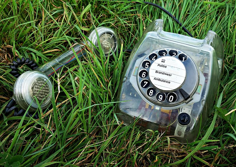 Gray rotary dial telephone on grass