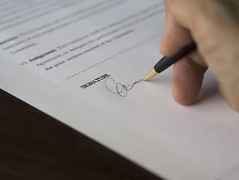 Person signing a paper with black pen close up photo